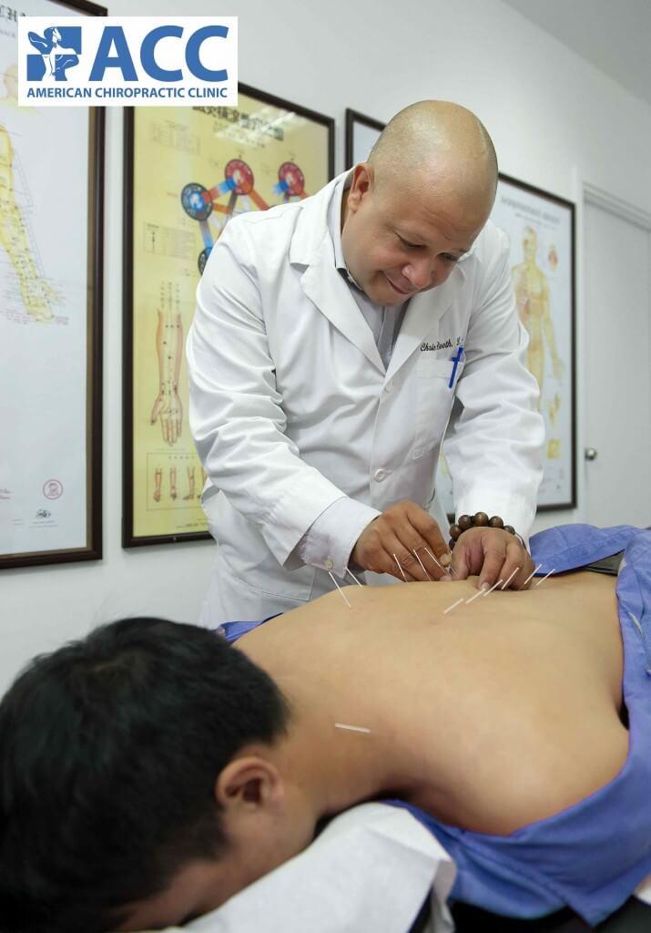 Bác sĩ đang châm cứu cho bệnh nhân đau cột sống lưng