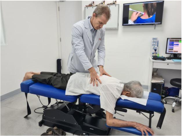 Bác sĩ Tim Gallivan kiểm tra nắn chỉnh cột sống cho bệnh nhân
