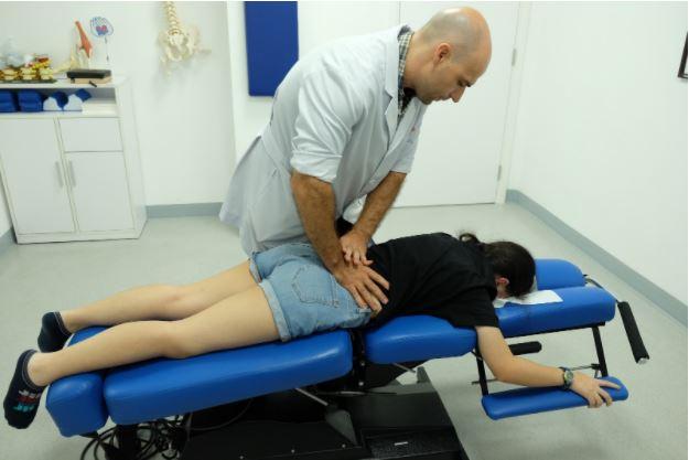 Bác sĩ Will Gunson nắn chỉnh cột sống lưng cho bệnh nhân nhí